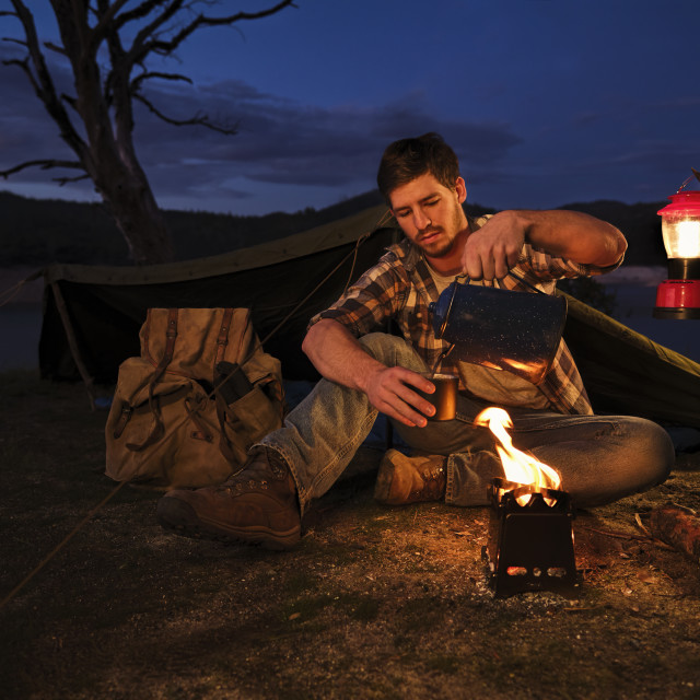 """Youn Man Camping and Drinking Coffee By A Camp Fire"" stock image"