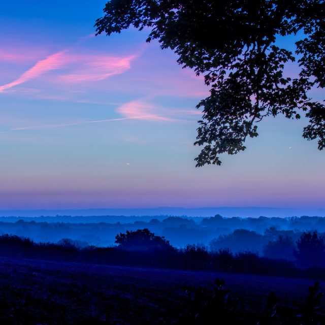 """Blue skies dawning. Early morning mist."" stock image"