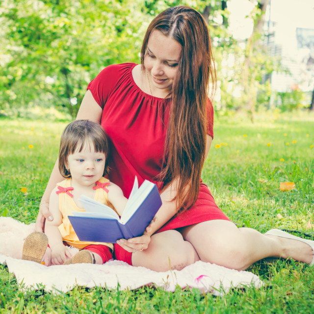 """""""Mother and daughter reading book outdoors"""" stock image"""
