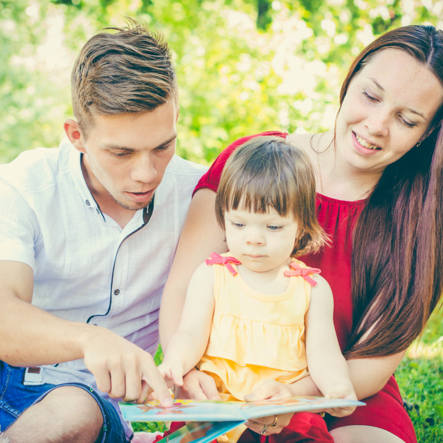 """""""Parents and daughter reading book outdoors"""" stock image"""