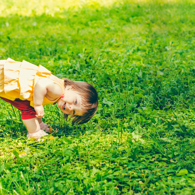 """""""One-year baby girl playing upside down on street"""" stock image"""