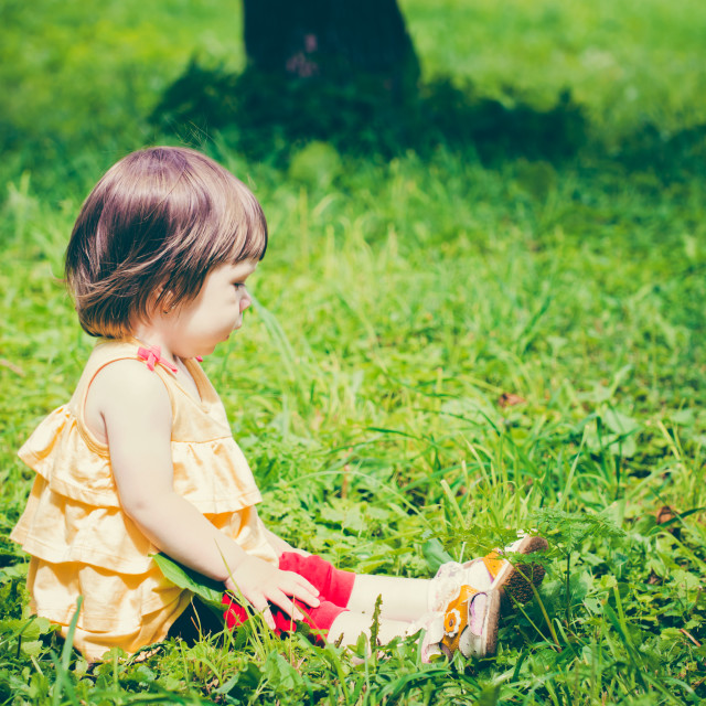 """""""One-year baby girl sitting on grass"""" stock image"""