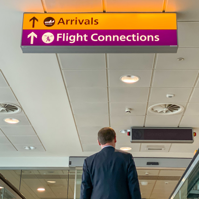 """""""Person arriving at Heathrow Airport in London walking under signs showing travellers the way to the Arrivals Hall and Flight Connections."""" stock image"""