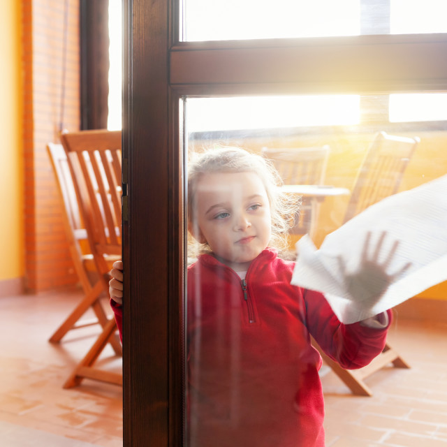 """Three year old girl helps with housekeeping by cleaning the windows."" stock image"