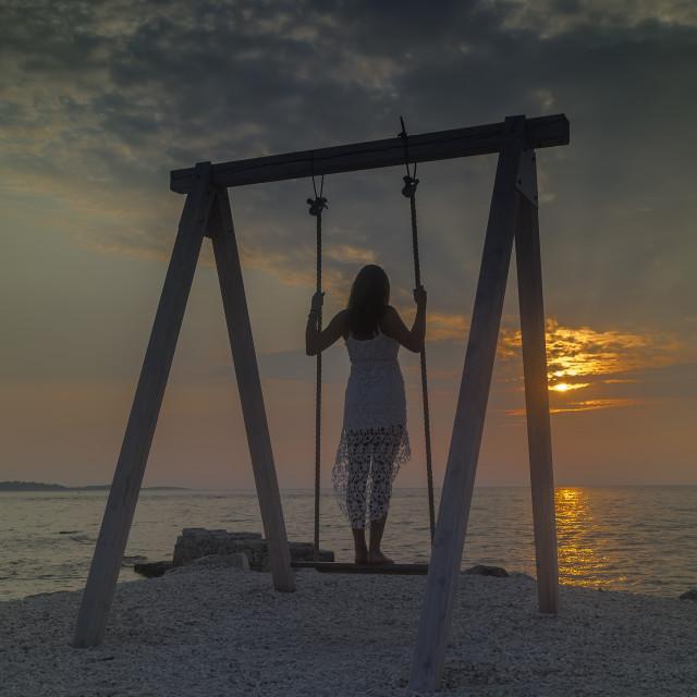 """Girl standing on wooden swing"" stock image"