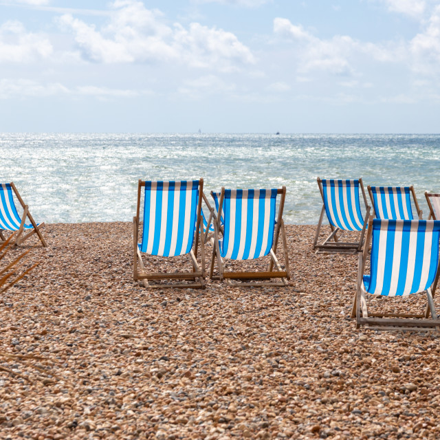 """Colourful striped deck chairs on Brighton beach, England"" stock image"