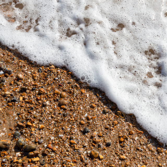 """Waves lapping the pebbles on Brighton beach"" stock image"