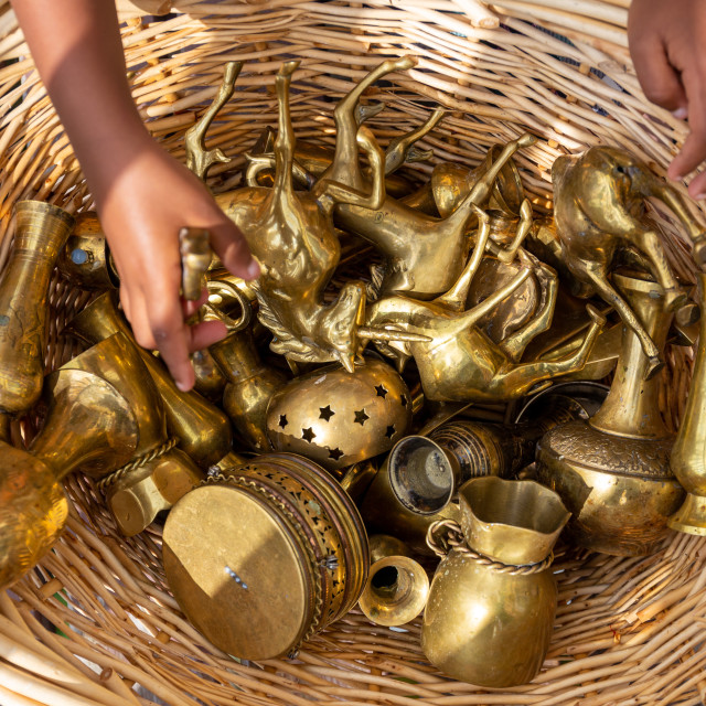 """Child hands with a variety of brass collectible objects"" stock image"