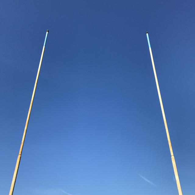 """""""Rugby posts isolated against a deep blue sky, with space for copy"""" stock image"""