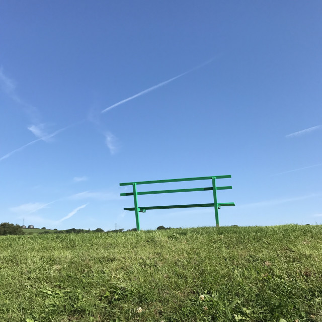 """""""Wooden bench in a public park isolated against deep blue sky. Space for copy"""" stock image"""