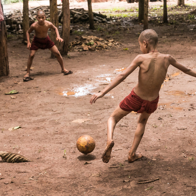 """Young monks playing football"" stock image"