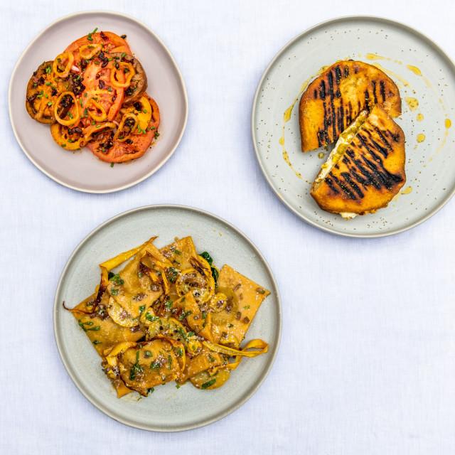 """Trio of heirloom tomatoes, cheese toast and ravioli"" stock image"