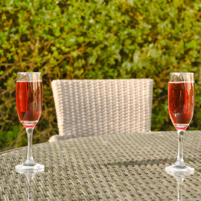 """Pink champagne in two flute glasses on a glass table top"" stock image"