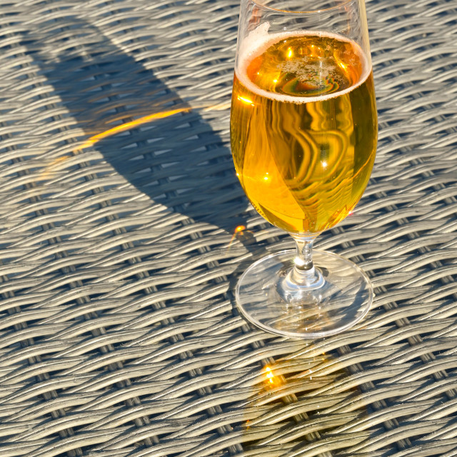 """Glass of golden beer lager on the glass table top"" stock image"