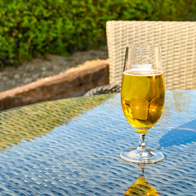 """Glass of golden beer lager on a glass table top"" stock image"