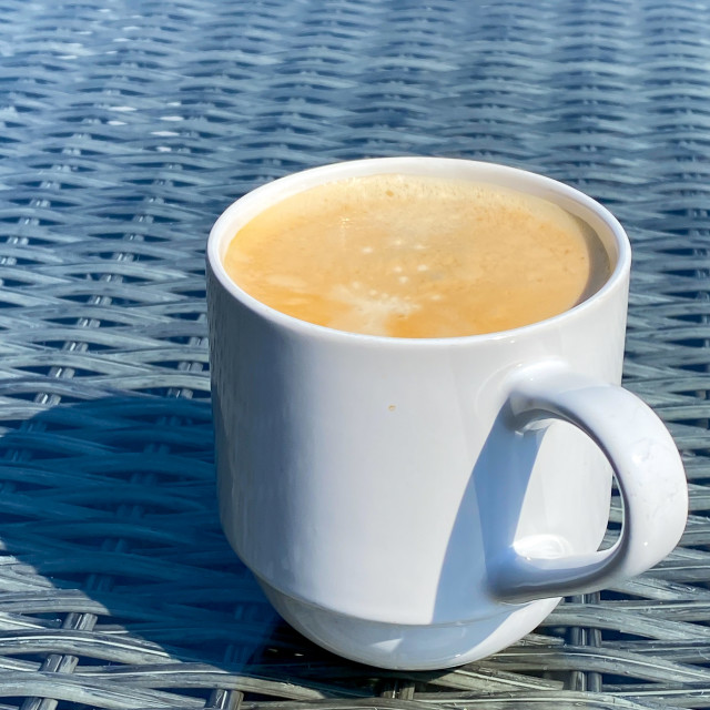 """White mug with hot frothy coffee on a glass table top"" stock image"