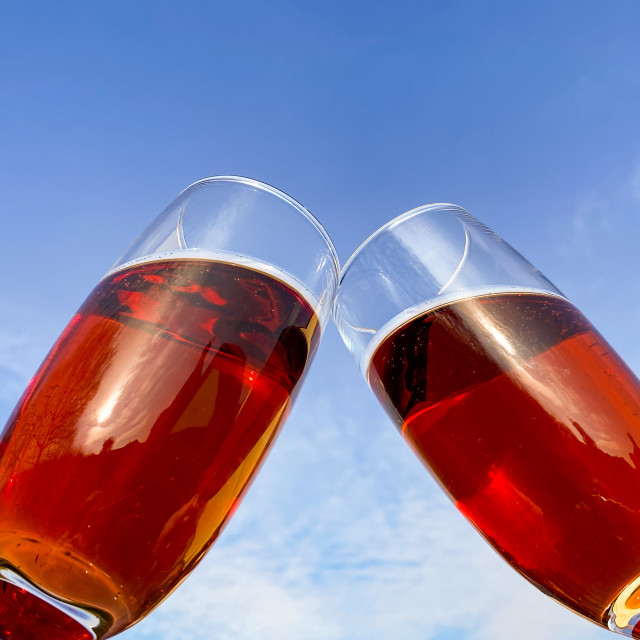 """A toast of pink champagne against a deep blue sky"" stock image"