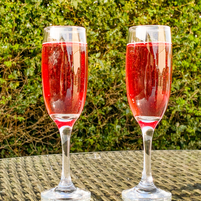 """Pink champagne in two flute glasses side by side on a glass table top"" stock image"