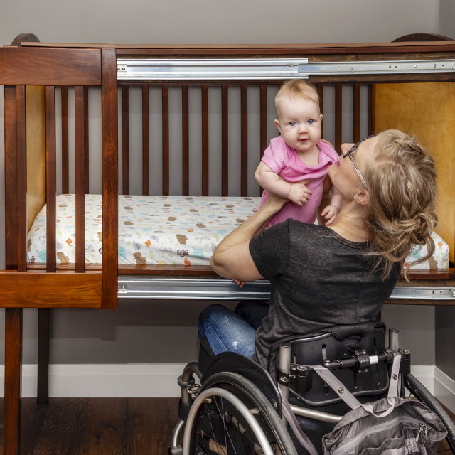 """""""A paraplegic mother picking her baby up after a sleep in a customized crib..."""" stock image"""