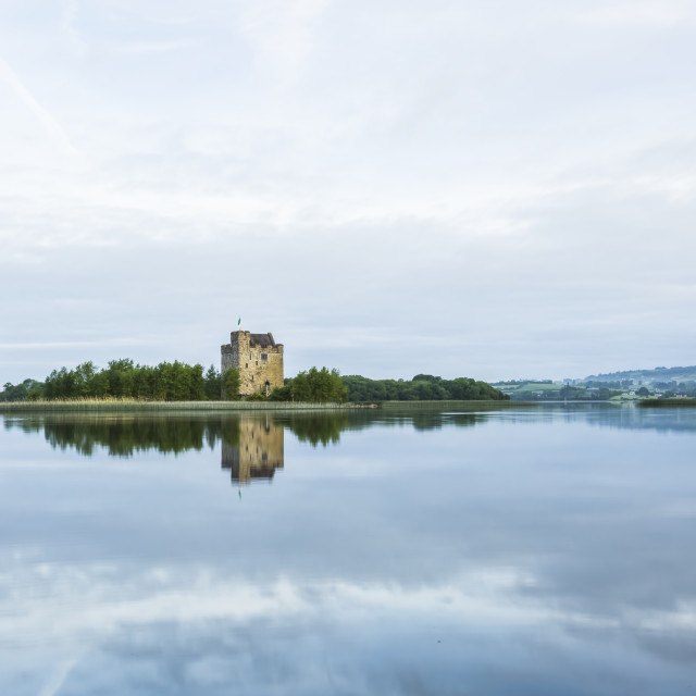 """""""Symmetrical reflections of Castlebawn tower house on Lough Derg on a summer..."""" stock image"""