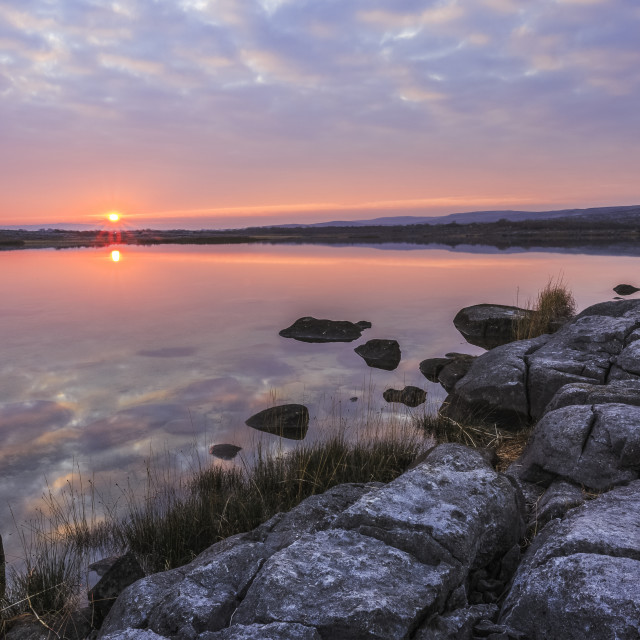 """""""Sun setting over lake with reflections on a cloudy evening with limestone..."""" stock image"""