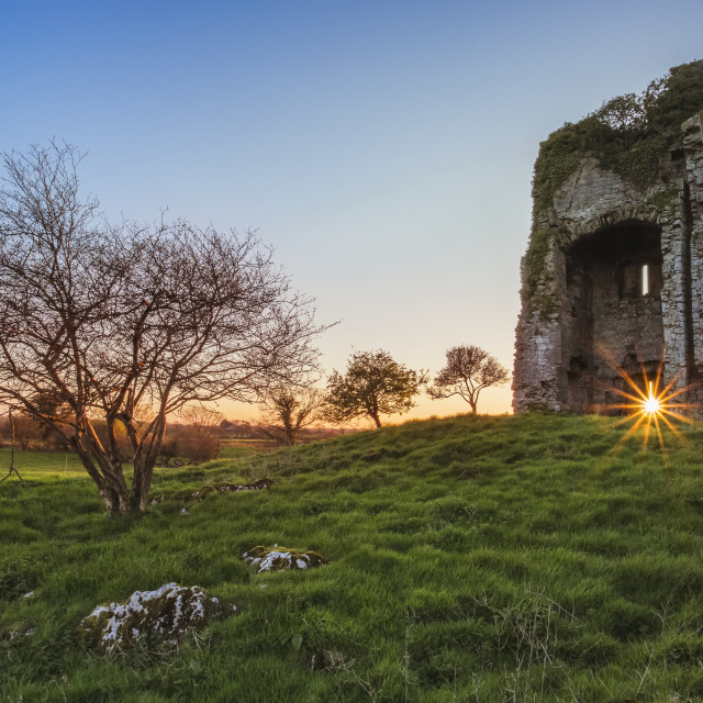 """""""Old Irish castle ruins in a green field with the setting sun coming through..."""" stock image"""