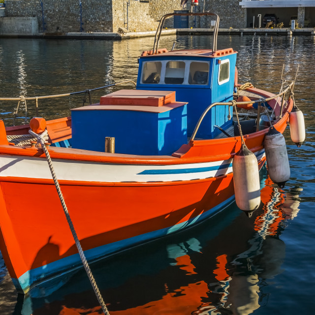 """""""Small traditional orange, white and blue Greek fishing boat with boat fenders..."""" stock image"""