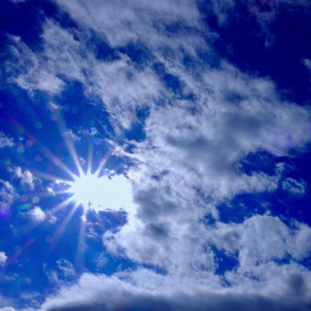 """Cloudy Blue Sky & Sunburst"" stock image"