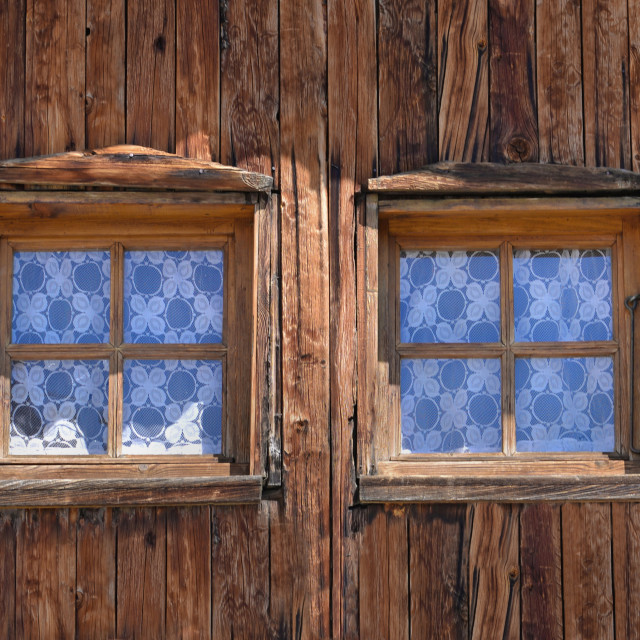 """""""close on two little windows on a wooden facade of old alpine chalet"""" stock image"""