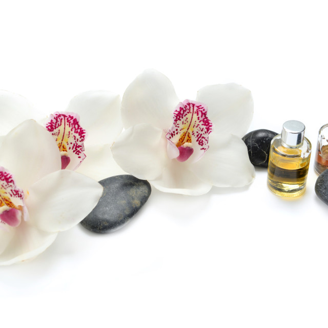 """""""oil bottles and pebbles with beautiful orchids on white backgro"""" stock image"""