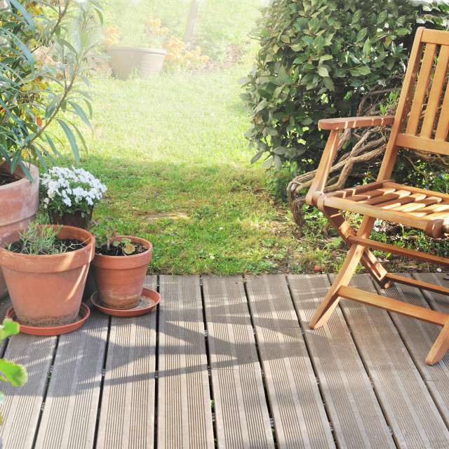 """""""chair and potted plant on wooden terrace in summer"""" stock image"""