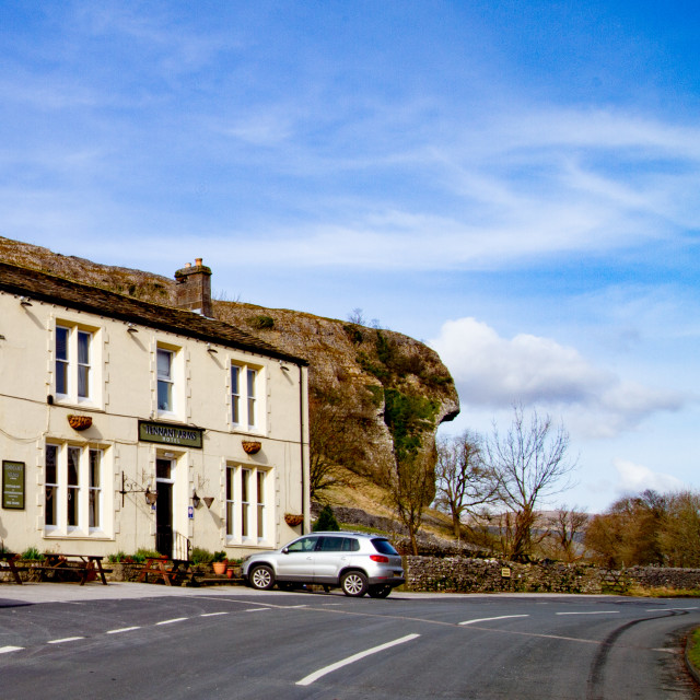 """Kilnsey Crag, Kilnsey, Upper Wharfedale. Tennants Arms Hotel to foreground."" stock image"