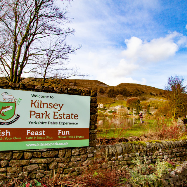 """Looking towards Kilnsey Crag from Road B6160, Kilnsey, Upper Wharfedale. Showing Sign to Kilnsey Park Estate."" stock image"