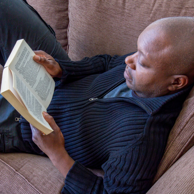 """Black man reading on the sofa"" stock image"