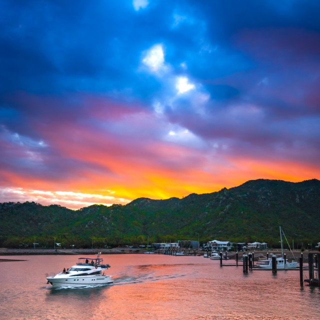 """A boat leaves the marina at Magnetic Island, Australia at sunset"" stock image"