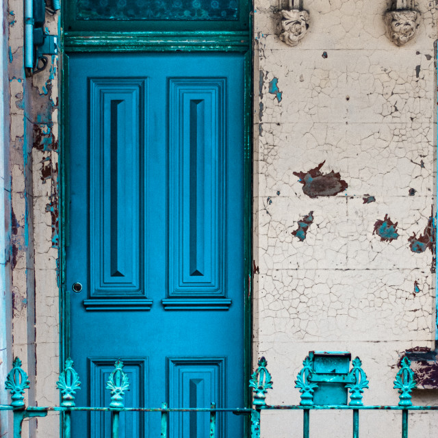 """Vibrant blue front foor in a terrace house with textured wall and railings"" stock image"