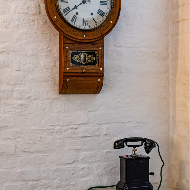"""""""Antique wooden telephone and clock on white wall"""" stock image"""