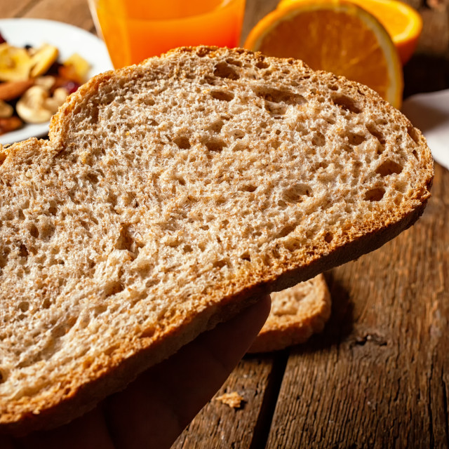 """Slice of organic wholemeal bread on rustic table."" stock image"