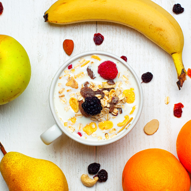 """Breakfast with bowl of milk, cereals and red fruits on white table and fresh..."" stock image"