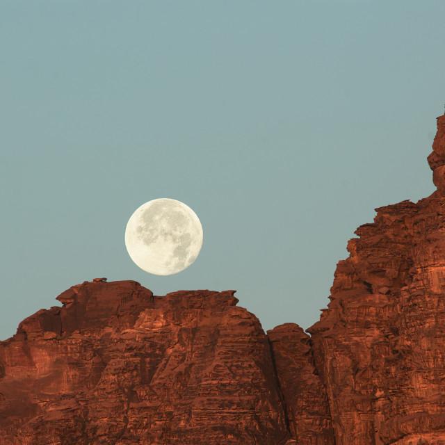 """Full moon setting over Wadi Rum"" stock image"