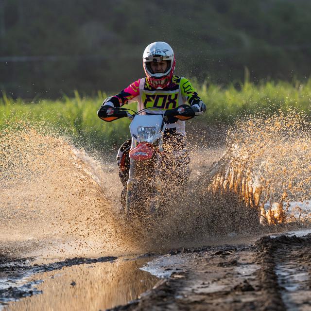 """Motorcycle riding through mud puddle"" stock image"