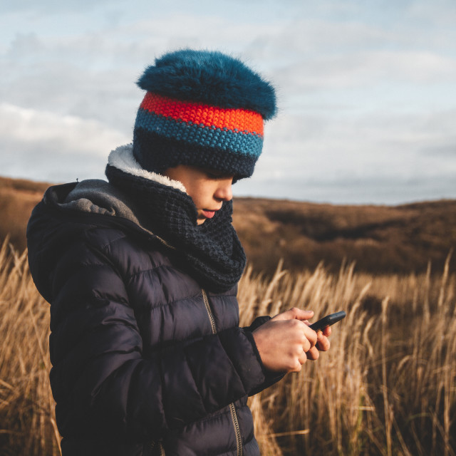 """""""Boy with a funny blue cap is using a mobile phone outdoors with a beautiful yellow grass background"""" stock image"""