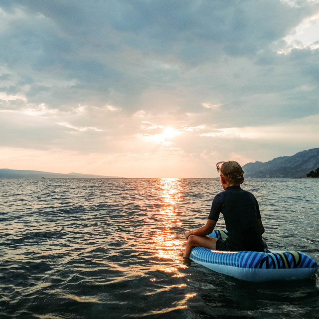 """""""A boy sitting on an inflatable raft floating on beautifully lit rippled water, Croatia"""" stock image"""
