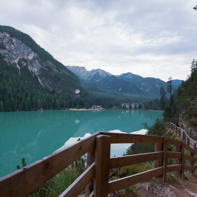 """""""Dirt path to staircase runs along the Braies Lake under a cloudy"""" stock image"""