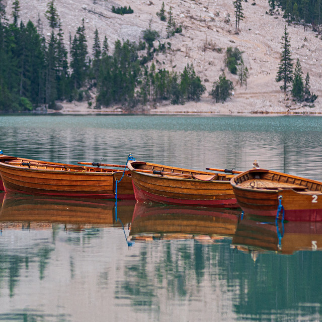 """""""Row of wooden boats tied up in the middle of Lake Braies at firs"""" stock image"""