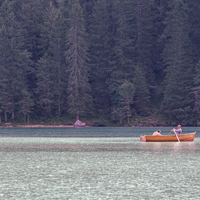 """""""Tourists paddle on a wooden boat on Lake Braies"""" stock image"""