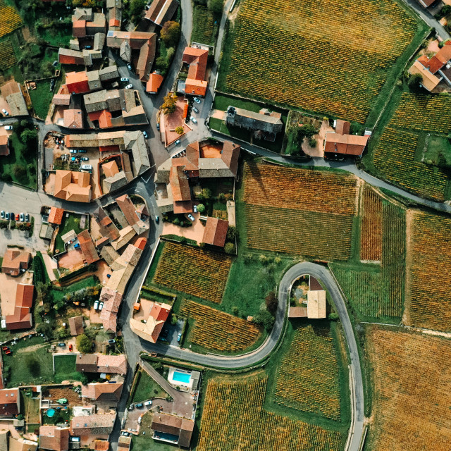 """""""Aerial shot of a French village with orange roofs, winding roads and surrounded by vineyards - stock photo"""" stock image"""