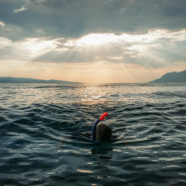 """""""A boy snorkelling in a beautifully rippled sea on a beach in Croatia"""" stock image"""