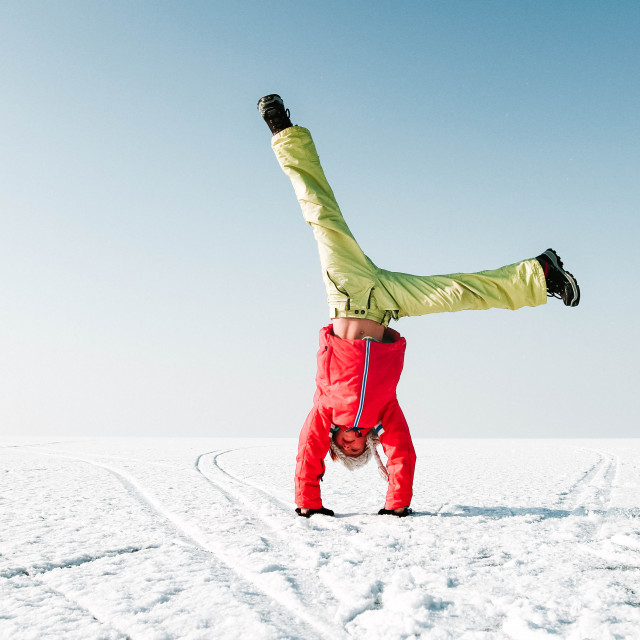 """""""A girl is doing a handstand and is having fun on a frozen lake in Austria"""" stock image"""