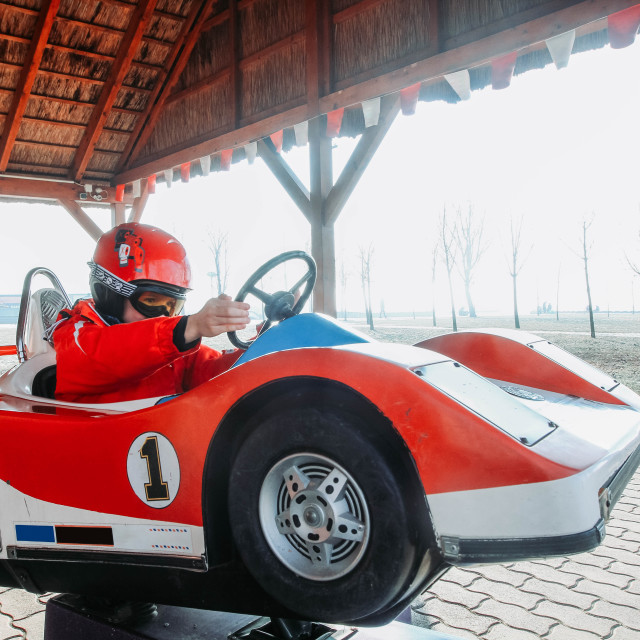 """""""Young boy in a helmet and goggles sitting in a red and white toy racing car"""" stock image"""